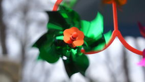 Green toy windmill is spinning from the wind stock video footage