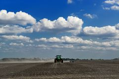 Green tractor cultivating a field with blue sky and clouds on th Stock Image