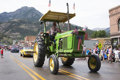 Green tractor drives in July 4 Independence Day Parade Royalty Free Stock Images