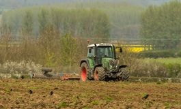Green tractor in field cultivating soil Royalty Free Stock Photos