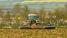 Green tractor in field cultivating soil Royalty Free Stock Photography