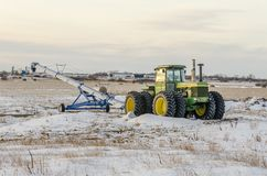 Green tractor and grain loader on the snow field Royalty Free Stock Photo