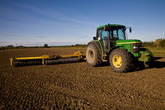 Green tractor with harrow on tilled field Royalty Free Stock Photography