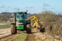 Green tractor hedge cutting and digger clearing a ditch Royalty Free Stock Photography
