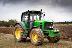 Green tractor. Karlovo, Bulgaria - August 22th, 2015: Ploughing a field with John Deere 6930 tractor. John Deere 8100 was manufactured in 1995-1999 and it has Royalty Free Stock Photo