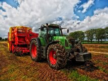 Green Tractor Pulling Red Bin on Field at Daytime Royalty Free Stock Image