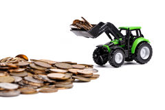 Green Tractor Raking Up Coins Royalty Free Stock Images