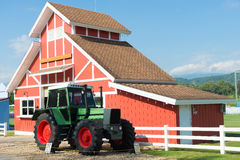 Green Tractor and Red Barn with blue sky and white fence. Stock Photos