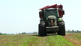 Green tractor with red loader wagon in the grain field and a clear blue sky. Prores, slow motion stock video footage