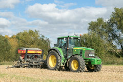 A green tractor with a seed drill in a stubble field Royalty Free Stock Photography