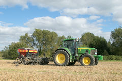 A green tractor with a seed drill in a stubble field Royalty Free Stock Image