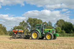 A green tractor with a seed drill in a stubble field Stock Photo