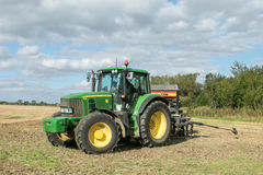 A green tractor with a seed drill in a stubble field Royalty Free Stock Images