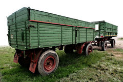 Green tractor trailers. Two green tractor trailers joined together. Trainers are parking on grass and the image has white background. The trailers are empty shot stock image