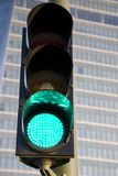 Green Traffic Light. Against modern office building background Stock Photo