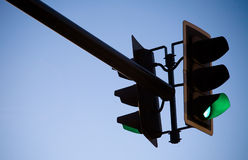Green Traffic Light. A green overhead traffic light with blue sky Stock Photo