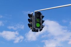 Traffic light with green light signal on sky background. Green traffic light against a blue sky and clouds. Suspended device stock photo