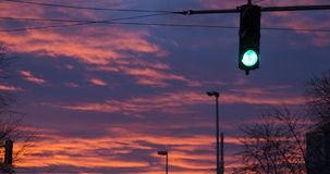 Green traffic light on the background of the clouds. During the sunset in the early evening Royalty Free Stock Photography