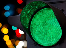 Green traffic light with colorful unfocused lights Royalty Free Stock Photo