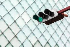 Green traffic light with glass windows of building in background Royalty Free Stock Image