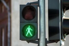 Green traffic light. Green pedestrian traffic light made of black plastic. The background is blurred stock photography