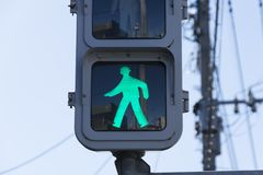 A green traffic light sign that says people can walk or pedestrian walking. This traffic sign was taken in Japan. royalty free stock image