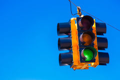 A green traffic light with a sky blue background Stock Photos