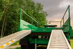 Green trailer in a field with ramp down by a forest. Concept heavy machinery delivery
