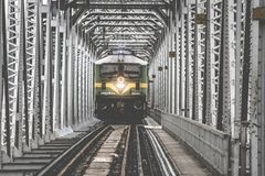 Green Train Coming Forward on White Metal Frame Stock Image