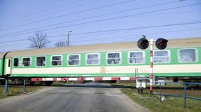 Green train crossing. A train crossing, blur motion, green car, some cables in the blue sky, warning traffic lights Stock Photos
