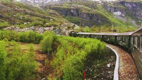 Green train drive in green forest in mountains. Hills. Greenery. Summer day. Landscape. Nature