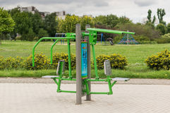 Green training machine. Green fitness machine for arm work out at a park on a cloudy day on August 2017 in Poznan, Poland Stock Photo