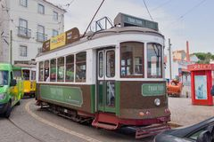 Green tram in narrow, curvy street, Lisbon Stock Image