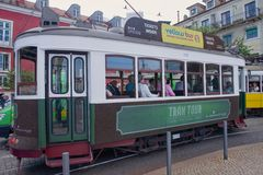 Green tram in narrow - Lisbon Stock Image