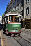 Green tram on a narrow street in Lisbon, Portugal Royalty Free Stock Images