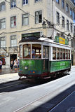 Green tram on a narrow street in Lisbon, Portugal Royalty Free Stock Photography