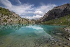 Green transparent mountain lake and beautifuk sky Royalty Free Stock Image