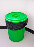Green trash bin. Green bin with black garbage bag and lid for sanitary Stock Photo