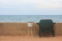 Green trash bin on the beach Stock Photo