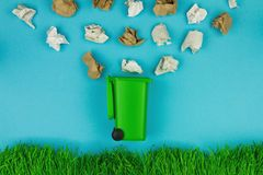 Green trash bin for paper as symbol of refuse reuse recycle concept. With green grass and isolated on blue background. Ecology, safe planet and environmental royalty free stock image