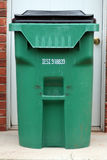 Green Trash Can. Large green trashcan sits in front of a white exterior door Royalty Free Stock Photos