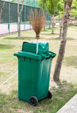Green trash can and coconut stick broom Stock Images