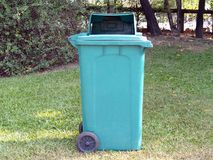 Green trash can garbage bin on green grass field in public park Stock Photography
