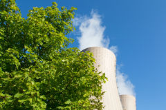 Green tree branches against a nuclear power plant Stock Photos