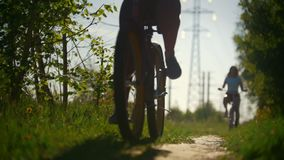 Green tree branches, girls walking on bicycles, green tree, sunny summer day. Slow-motion stock footage