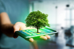 Green tree going out of a smartphone - Ecology concept. View of a Green tree going out of a smartphone - Ecology concept Stock Photos