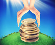 Green tree growing from pile of coins between hands Stock Photography