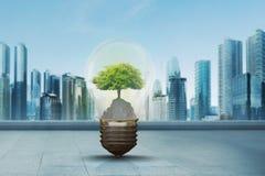 Green tree inside light bulb against modern city Stock Photo