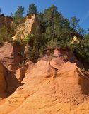Green trees create beautiful contrast with the ocher. Unique red and orange hills in the province of Roussillon, France. Green trees create a beautiful contrast royalty free stock photos