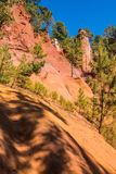 Green trees create contrast from ochre. Multi-colored outcrops - from yellow to red-orange. Green trees create beautiful contrast from ochre. Roussillon, Red stock photos